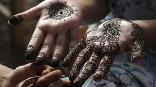 A girl gets her hands painted with henna in preparation for Eid al-Fitr