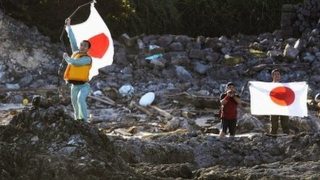 Members of a Japanese nationalist group raise Japanese flags after landing on disputed islands