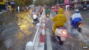 Motorists manoeuvre through a flooded street in Hanoi, Vietnam (image from 18 August 2012)
