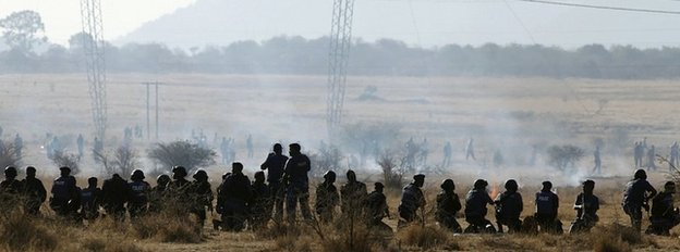 Policemen fire at striking miners at the Marikana platinum mine in South Africa on 16 August