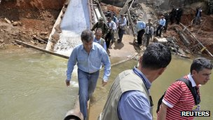 Colombian President Juan Manuel Santos visits the scene of a rebel attack in Caqueta province