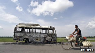 A man rides a bicycle in front of a bus that was burnt by a mob on the national highway near Rongia town in the northeastern Indian state of Assam in this August 16, 2012 file photo