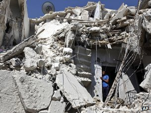 A man looks out of a house that has been shelled in Aleppo (19 August 2012)