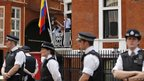 British police officers stand nearby as Wikileaks founder Julian Assange makes a statement to the media and supporters at a window of Ecuadorean embassy in central London.