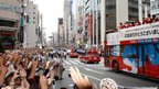 Japan's medallists at the London 2012 Olympic Games wave to a crowd of people from open-top buses during a parade in Tokyo's Ginza