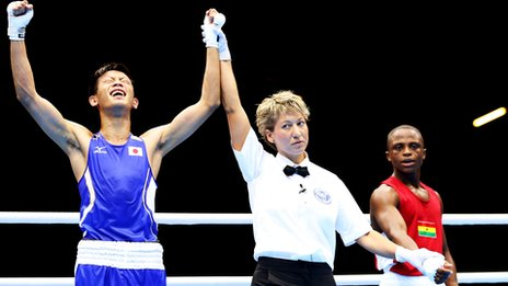 Satoshi Shimizu of Japan (L) celebrates victory over Isaac Dogboe of Ghana during their Men's Bantam Weight (56kg) bout on Day 1 of the London 2012 Olympic Games