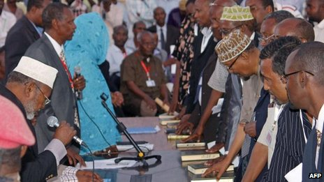 Members of Somalia&#039;s new parliament place their hands on the Koran as they are sworn in at Mogadishu&#039;s international airport 