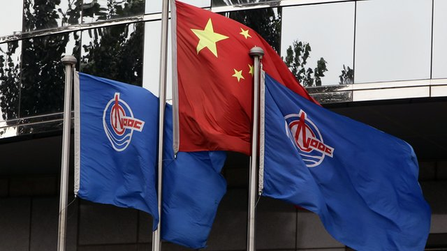 China National Offshore Oil Corp flags and China's flag in front of CNOOC's Beijing headquarters