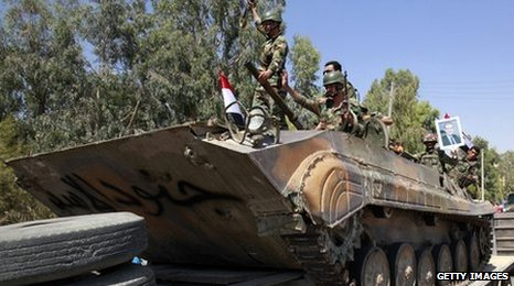 Syrian troops on a tank that says 'The soldiers of Assad'