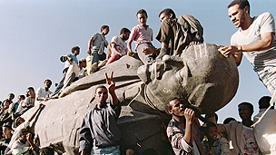 Ethiopians celebrate the end of an era on a toppled statue of the