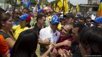 Venezuelan opposition candidate Henrique Capriles greets supporters during an election rally