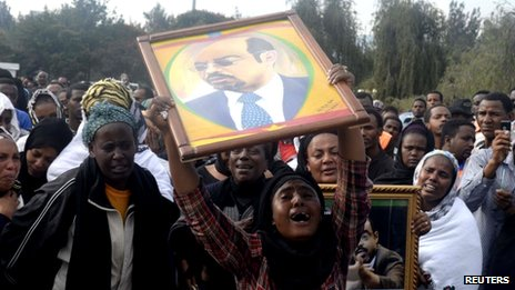 A woman wails while lifting a portrait of Ethiopia's Prime Minister Meles Zenawi as she waits for the arrival of his remains in Ethiopia's capital Addis Ababa, 21 August 2012