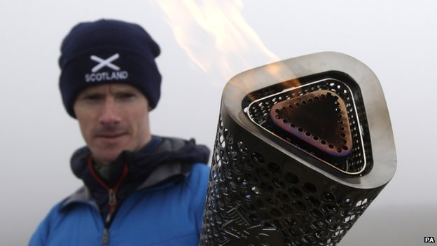 Mountaineer Kevin Shields carries the Scottish Paralympic Flame on top of Ben Nevis