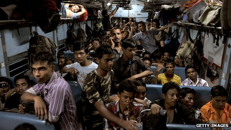 Indian migrant workers pile into a train as they flee Bangalore