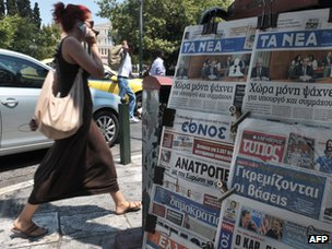 Woman walking past Greek newspapers