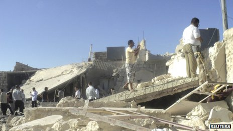 Residents inspect houses said to have been wrecked in an air strike in Mara, near Aleppo in Syria, 20 August