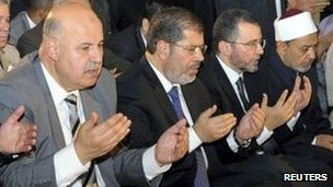 Egypt's President Mohammed Morsi (C) takes part in Eid al-Fitr prayer with Vice President Mahmoud Mekky (L) and members of the government in Cairo