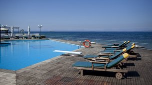 Empty poll and sun loungers at Greek hotel