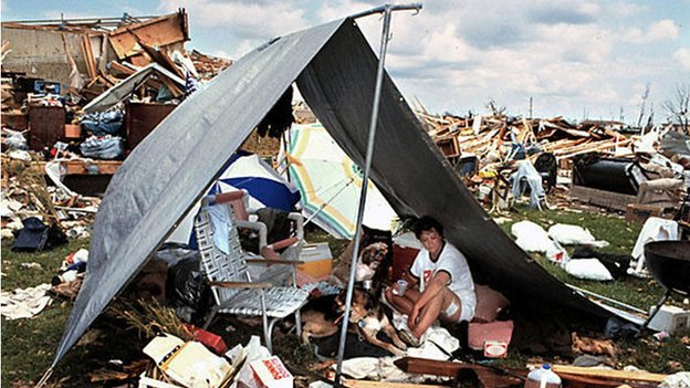 A woman with her dog in a tent admits hurricane rubble