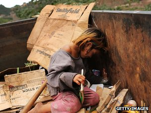 A street child plays in a dumpster in Honduras