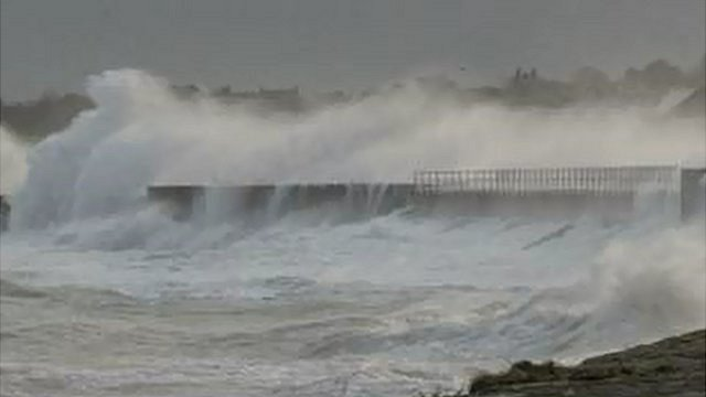 Waves crash over a Guernsey sea wall