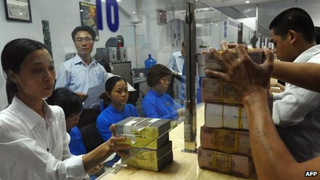 A branch of ACB bank in Vietnam's capital Hanoi shows staff transferring blocks of dong to customers on 23 August 2012