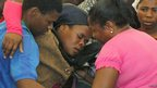Relative is assisted during a memorial service for miners killed during clashes at Lonmin&#039;s Marikana platinum mine. 23 Aug 2012