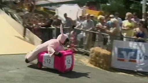 Man in a pink rabbit costume riding an upturned pink wheelie bin