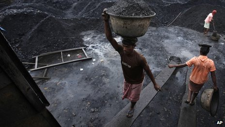 Workers load coal onto a truck at a coal depot in Gauhati, India,