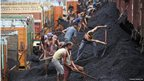 Indian labourers load coal onto trucks at a depot on the outskirts of Jammu, India,