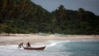 Fishermen launch their small wooden boat in Barahona, Dominican Republic