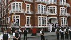 British police officers stand nearby as WikiLeaks founder Julian Assange makes a statement to the media and supporters at a window of Ecuadorian Embassy in central London.
