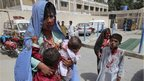 An injured mother carries her wounded children to a local hospital in Quetta