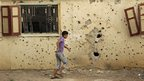 A boy walks past a building damaged by rocketfire in Tripoli (23 August 2012)