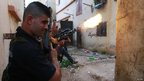 Sunni gunmen fire their weapons in the Bab al-Tabbana district in Tripoli (21 August 2012)