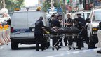 New York City Coroner's officers remove a body from the scene of the shooting