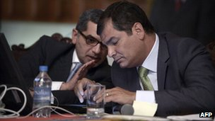 Ecuador's President Rafael Correa speaks with the country's press secretary