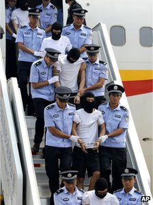 Hooded and hand-cuffed suspects are escorted to get off a plane after arriving in Beijing August 25
