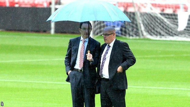 Managers Martin O'Neill and Brian McDermott under an umbrella