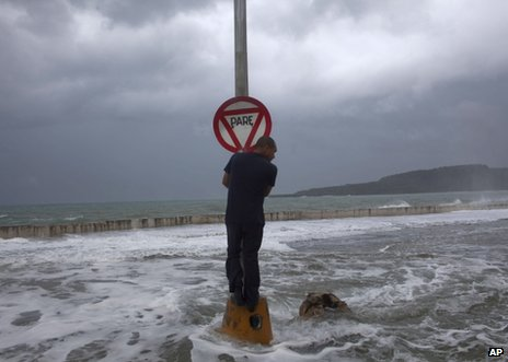 A man clings to a stop sign as waves pass over the seawall in Baracoa, Cuba, 25 August