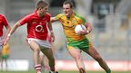Cork defender Eoin Cadogan attempts to halt the progress of Donegal forward Michael Murphy