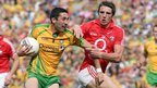 Rory Kavanagh of Donegal holds on to possession as Cork opponent Aidan Walsh challenges 