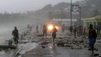 People run over a bridge covered by debris as waves hit the seawall in Barahona, Dominican Republic. Photo: 24 August 2012