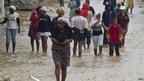 Residents leave flooded homes in a low-lying area affected by Tropical Storm Isaac in Port-au-Prince, Haiti 25/08/12