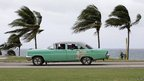 People ride a taxi as strong winds blow palm trees in Havana August 25, 2012.