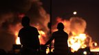Two boys watching the fire at the Amuay refinery