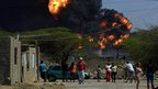 Local residents look at the fire after the blast at the Amuay refinery