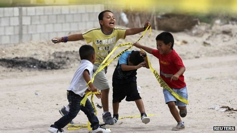 Children play with police tape from a crime scene in Ciudad Juarez where two people had been killed in July 2012