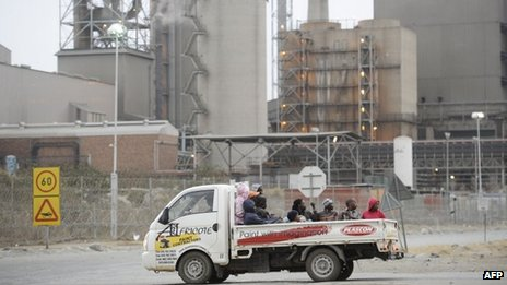 Workers in a truck pass on August 27, 2012 by the main entrance of the Lonmin platinum mine in Marikana