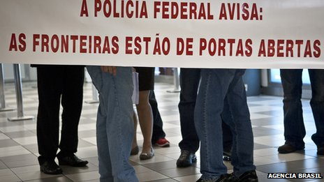 "A federal police sign at Guaraulhos International Airport warns: ""The borders are open"""